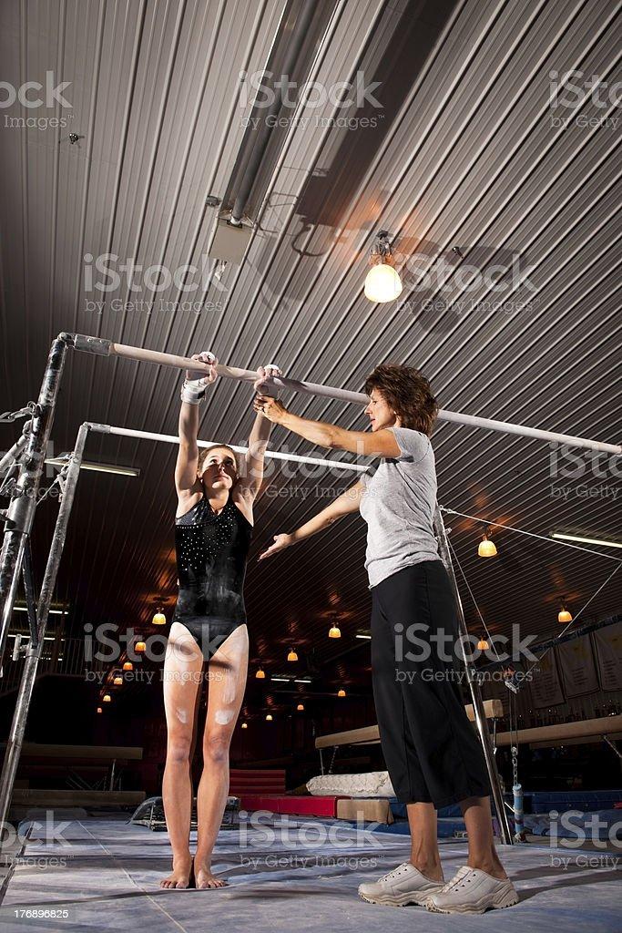 Gymnastics Coach Instructing Gymnast on Uneven Bars royalty-free stock photo