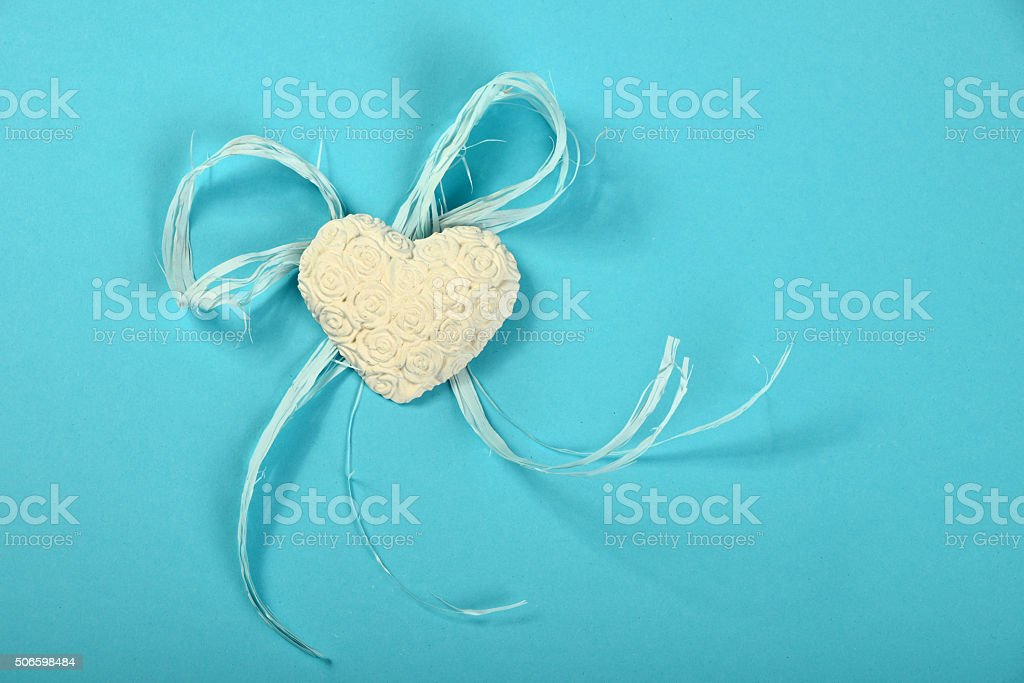 Gypsum heart with flowers and ribbon on blue background royalty-free stock photo
