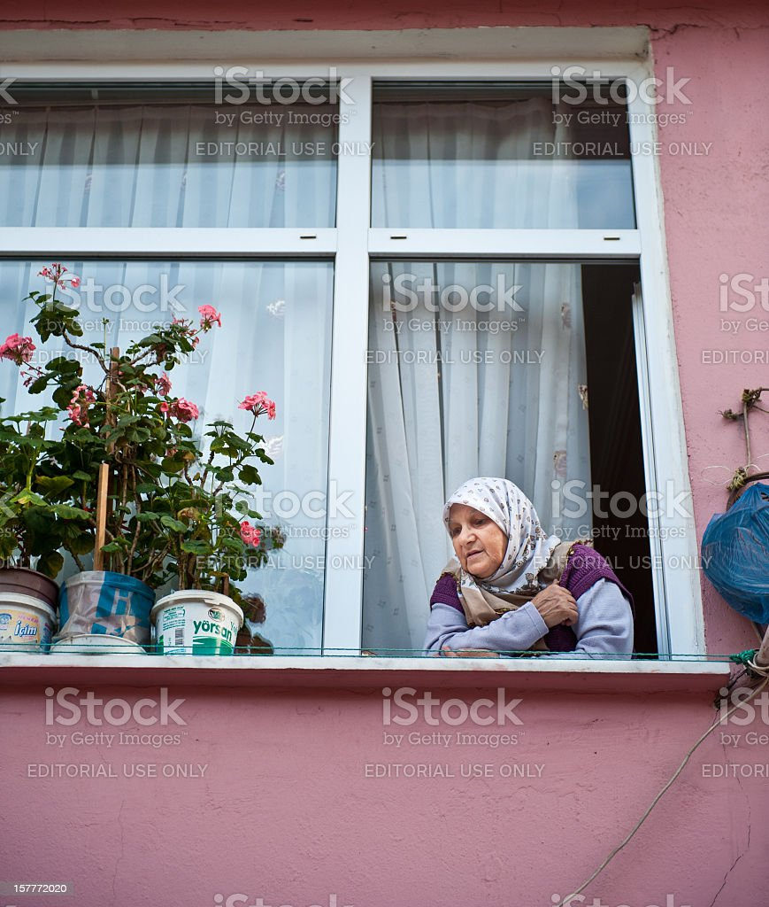 Gypsy looking out her window in Tarlabasi District Istanbul, Turkey stock photo