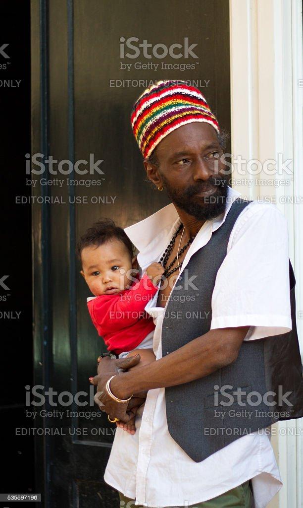 Haarlem, Holland: Man in Rasta Cap with Baby in Doorway stock photo
