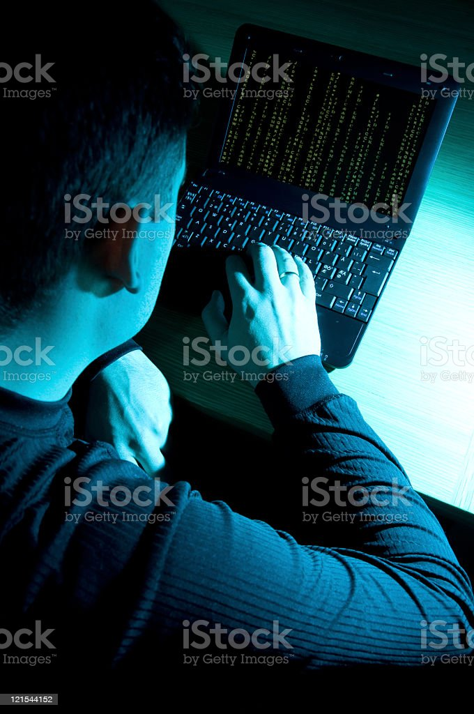 Hacker at work in front of a laptop computer royalty-free stock photo