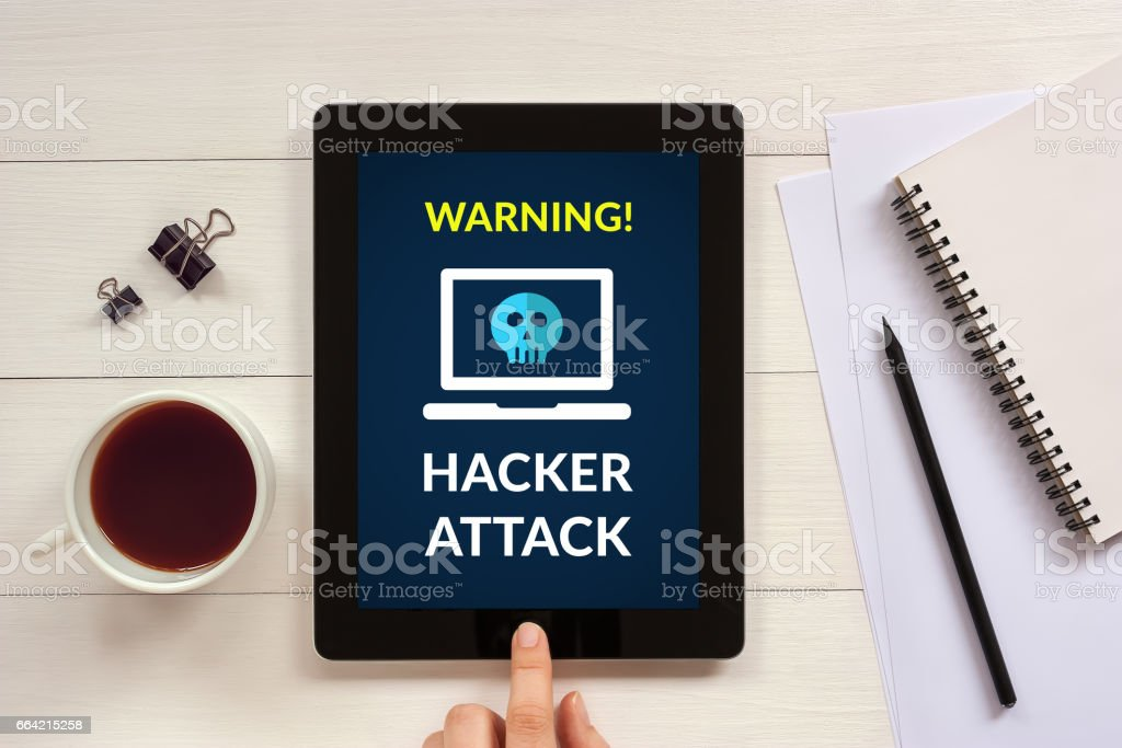 Hacker attack concept on tablet screen with office objects stock photo