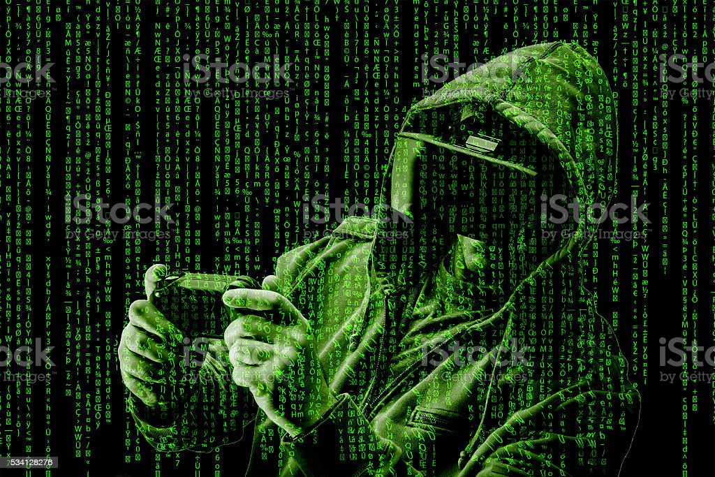 Hacker / gamer wearing a VR Helmet surrounded by green code stock photo