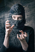 hacker girl in balaclava curled fingers makes cyber attack