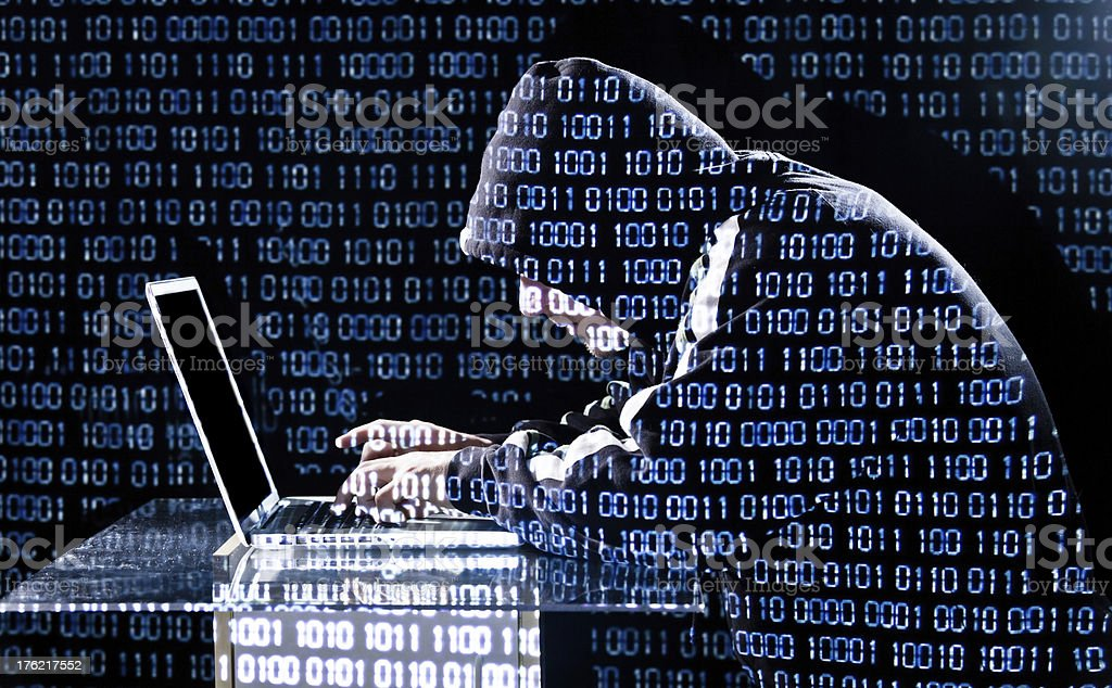 Hacker hacking through laptop in binary code background stock photo