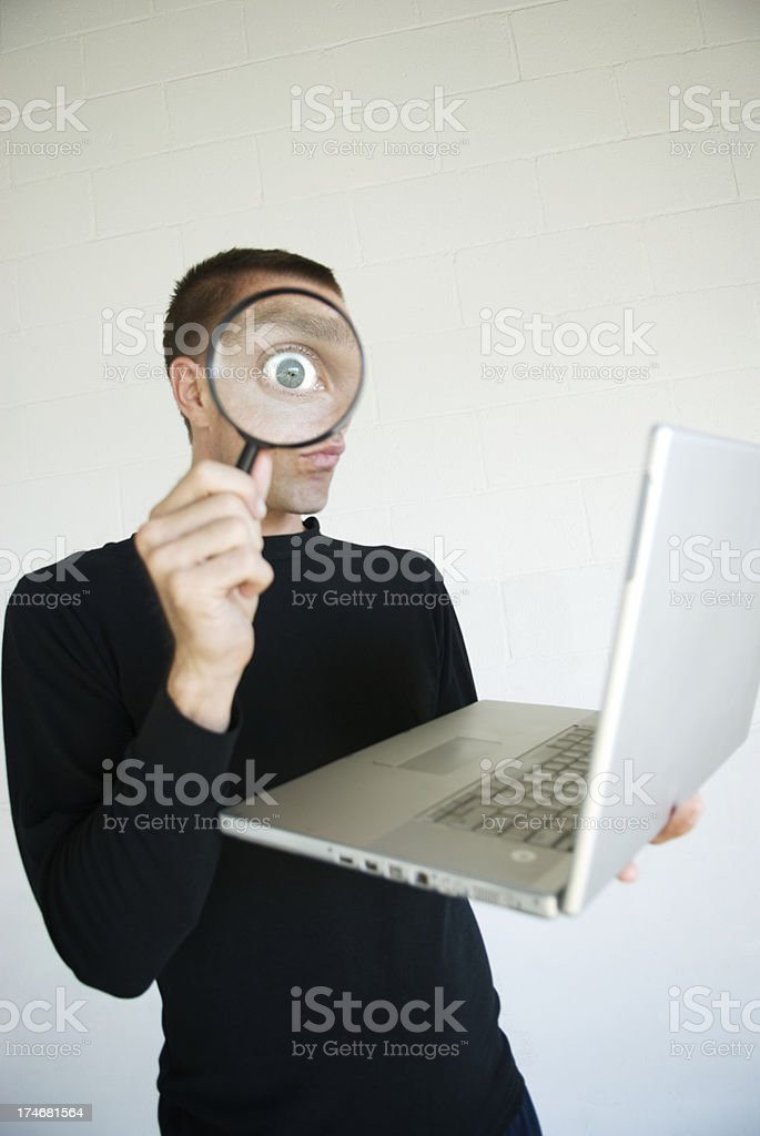 Hacker in Black Spying with Magnifying Glass on Laptop Computer royalty-free stock photo