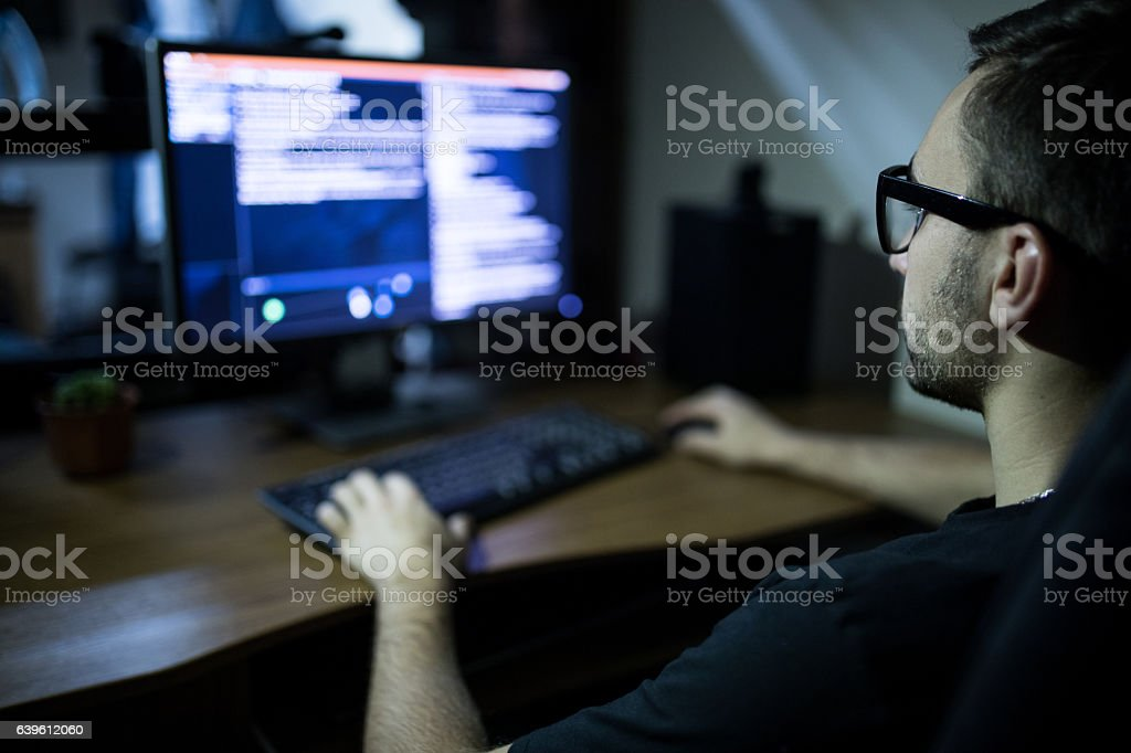 hacker in headset and eyeglasses with keyboard hacking computer system stock photo