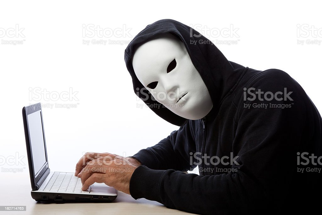 Hacker Man Wearing Mask And Hood Writing On Computer royalty-free stock photo