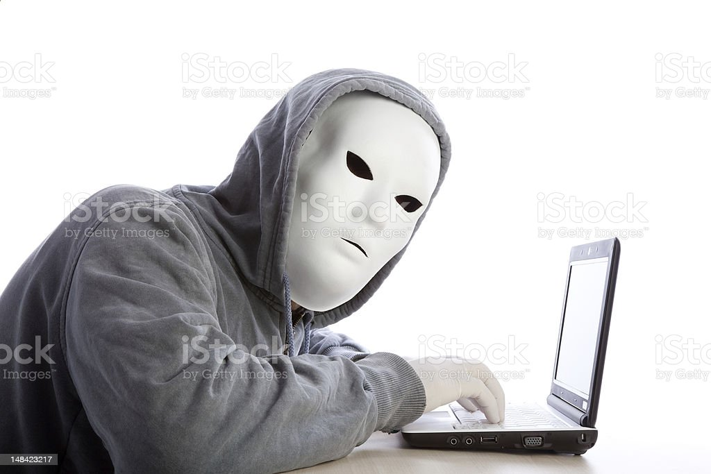 Hacker Man With Mask, Hood And Gloves Using Computer royalty-free stock photo