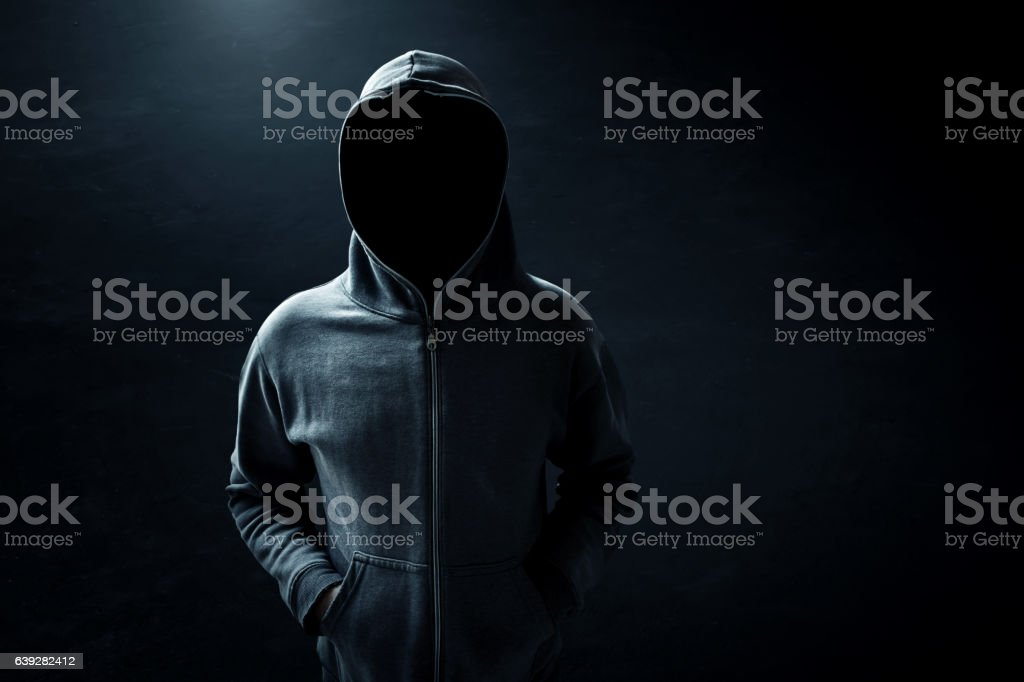 Hacker standing alone in dark room stock photo