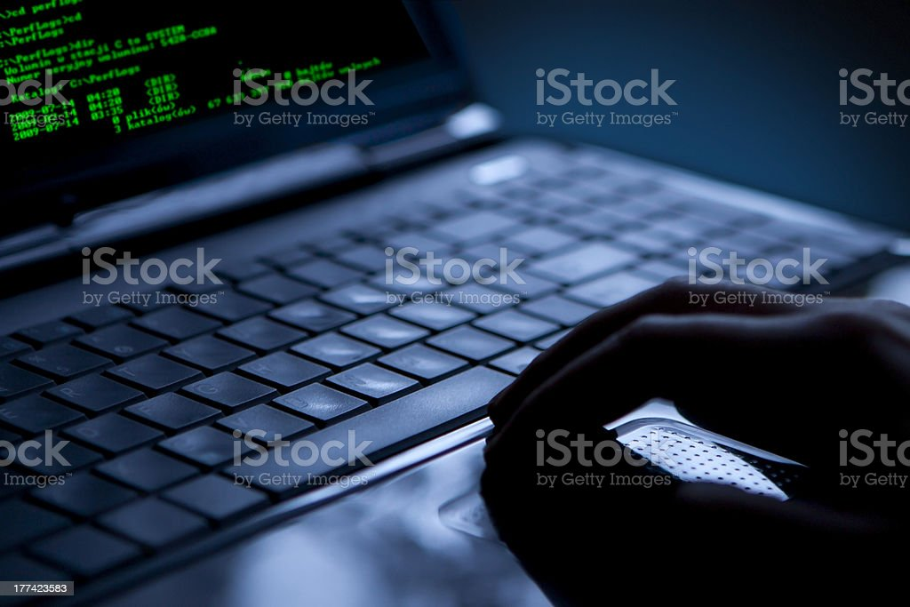 Hacker stealing data from a laptop royalty-free stock photo