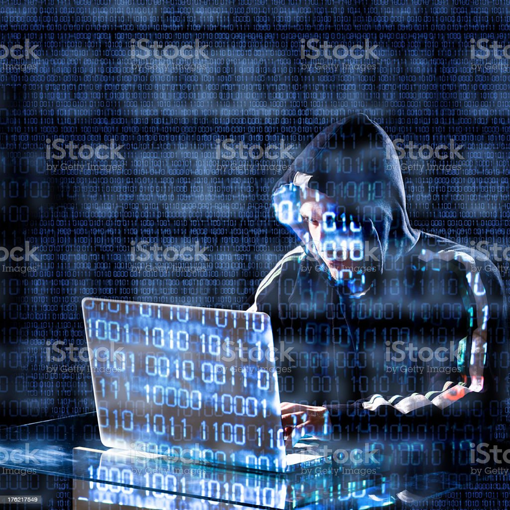 Hacker typing on a laptop with computer code overlay stock photo