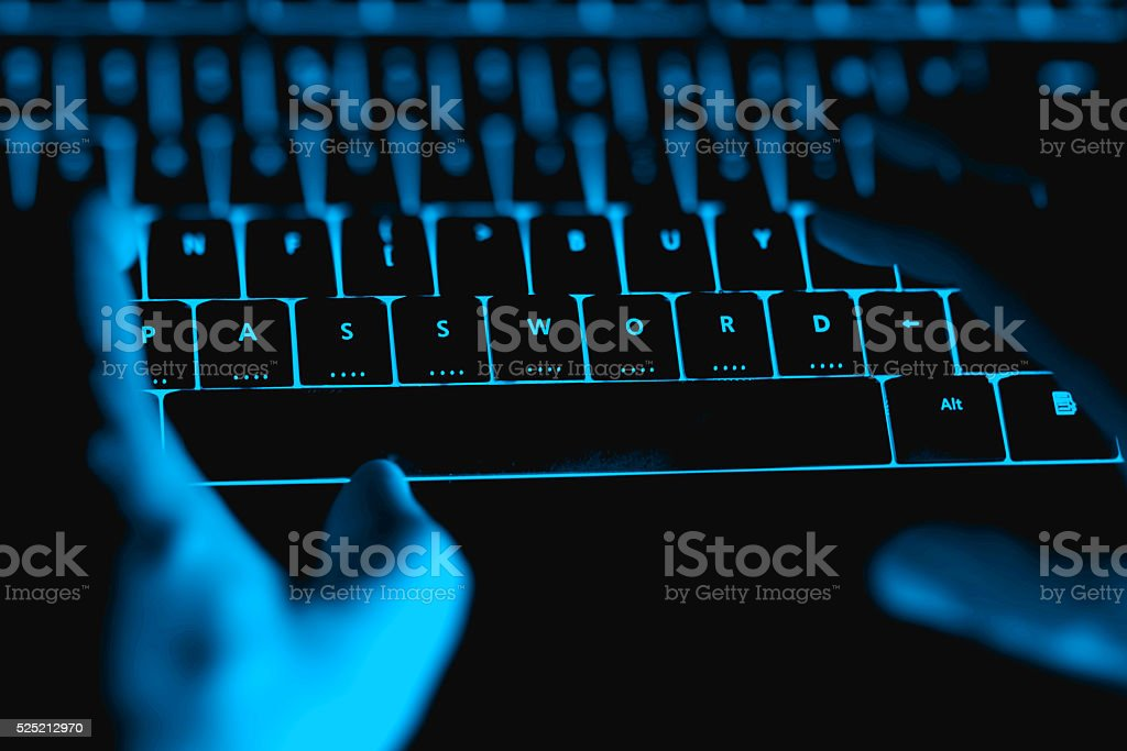 Hacker typing on the illuminated  keyboard by night. stock photo