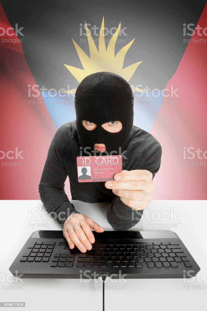 Hacker with flag on background holding ID card in hand - Antigua and Barbuda stock photo