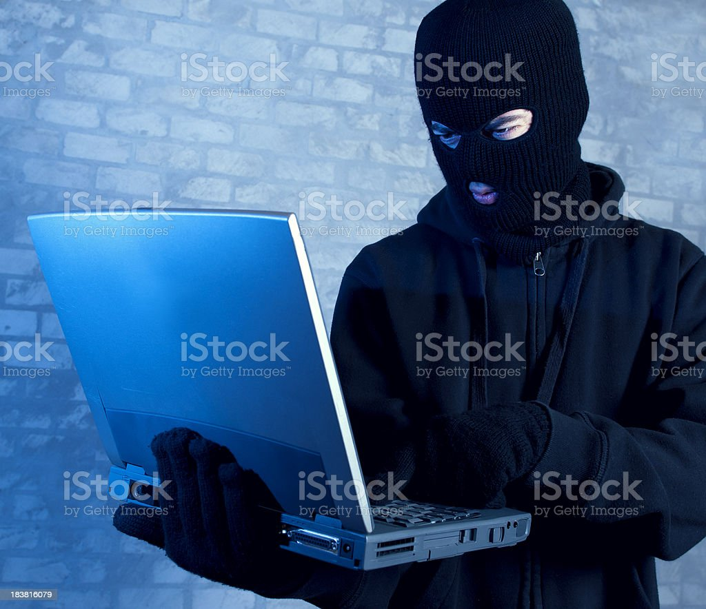 Hacker works on laptop at night stock photo
