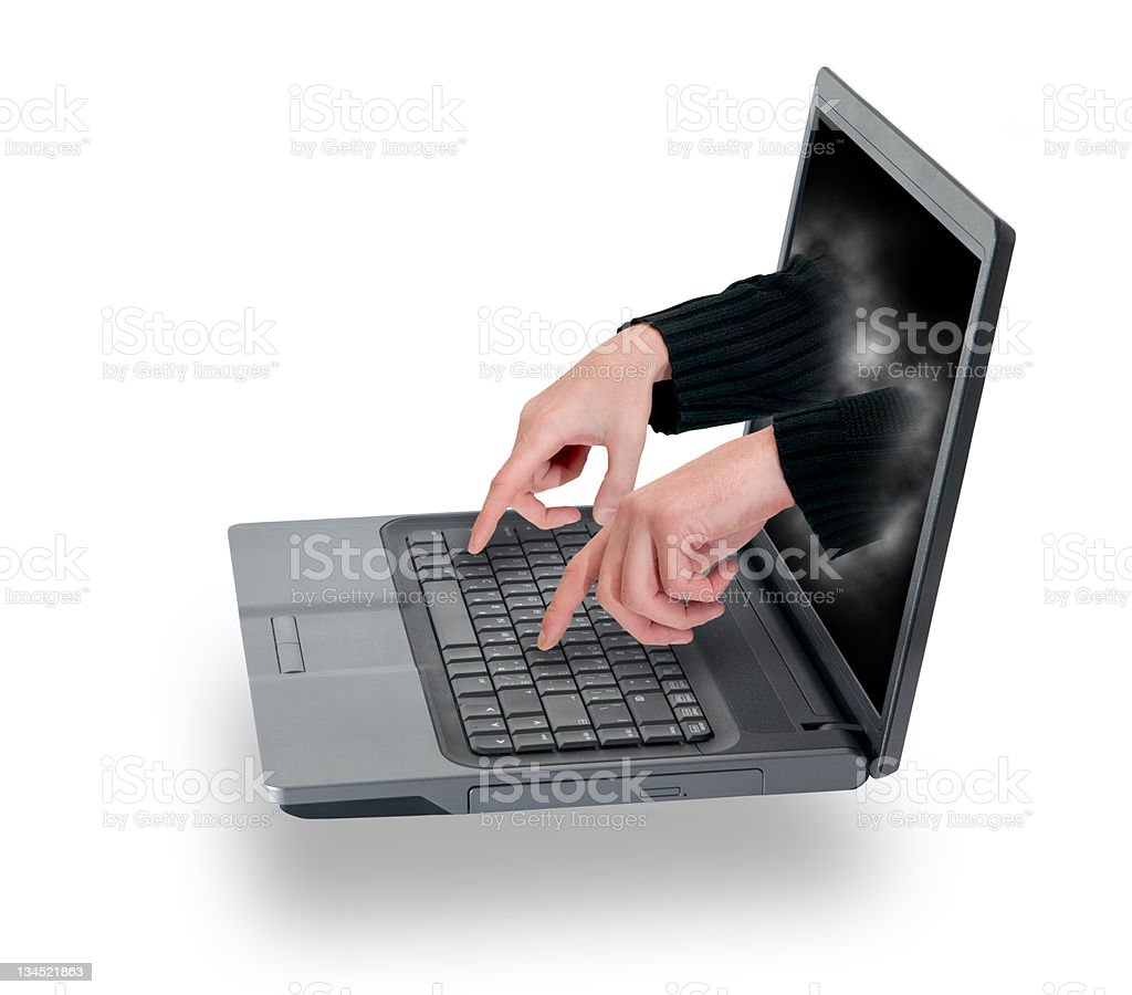 Hacker's hands are coming through laptop display royalty-free stock photo