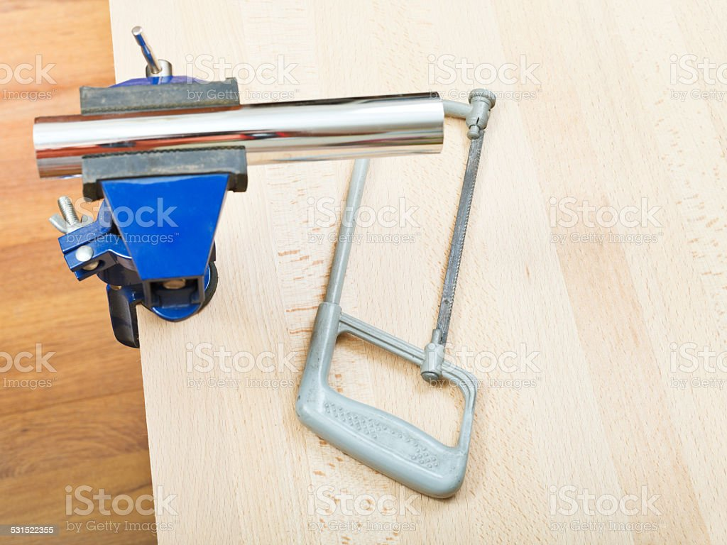 hacksaw and plumbing drain pipe gripped in vice stock photo