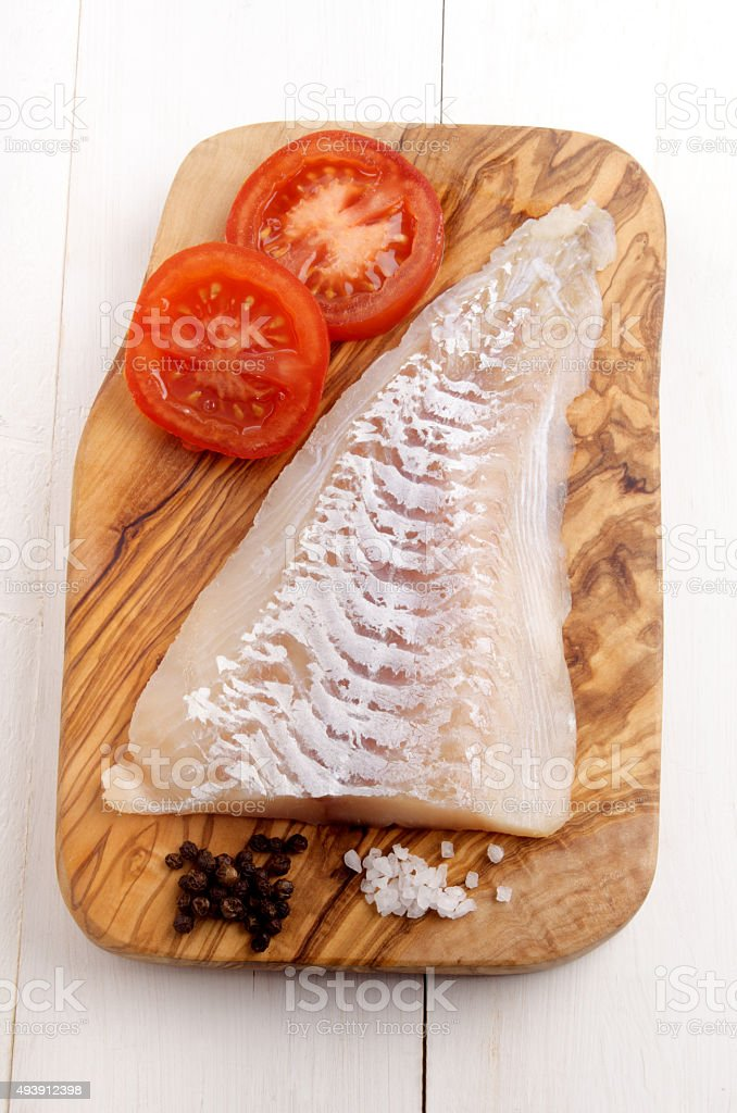 haddock fillet on a wooden board stock photo