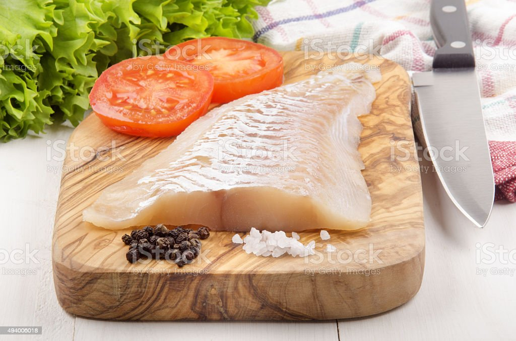 haddock fillet on a wooden board stock photo