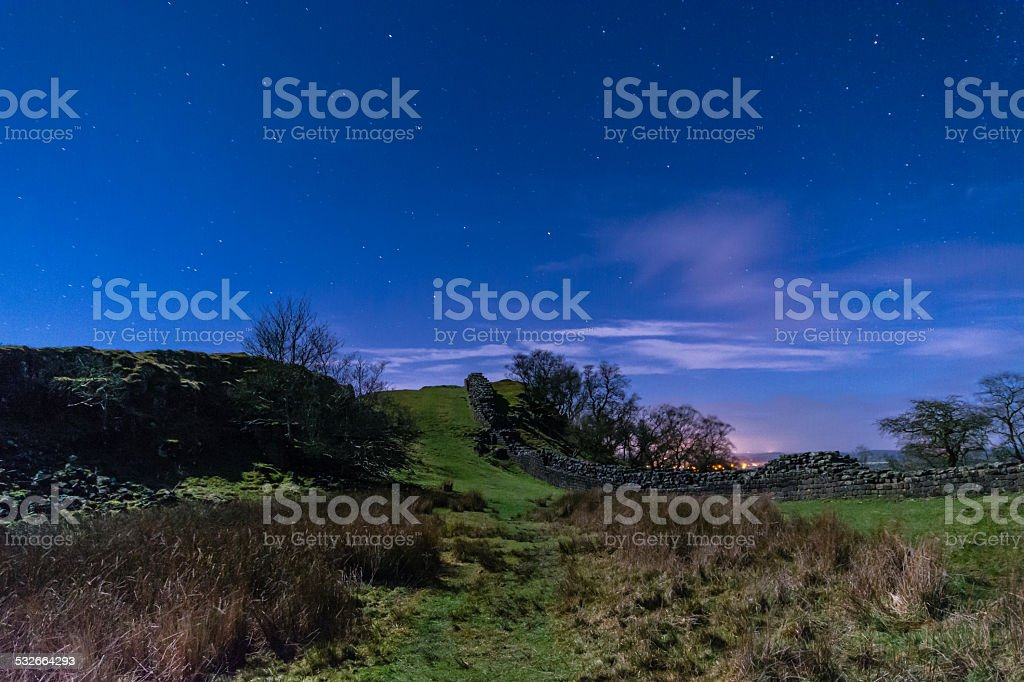 Hadrians Wall in a valley at night stock photo