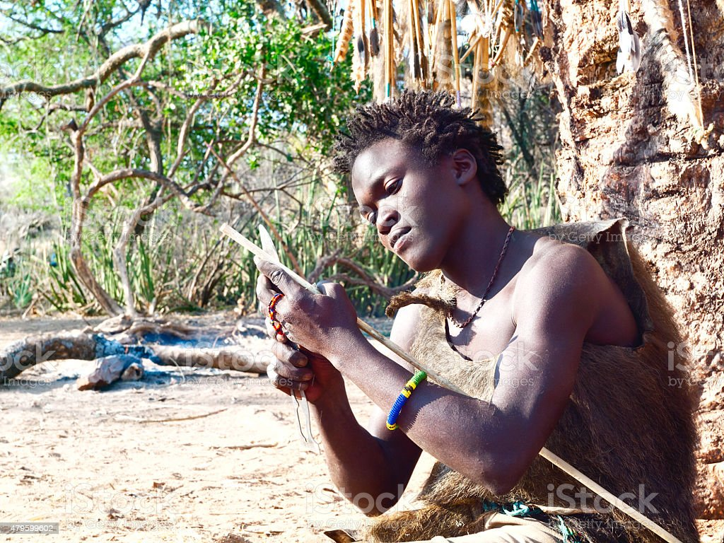 Hadzabe young bushman making the arrow for a hunting bow stock photo