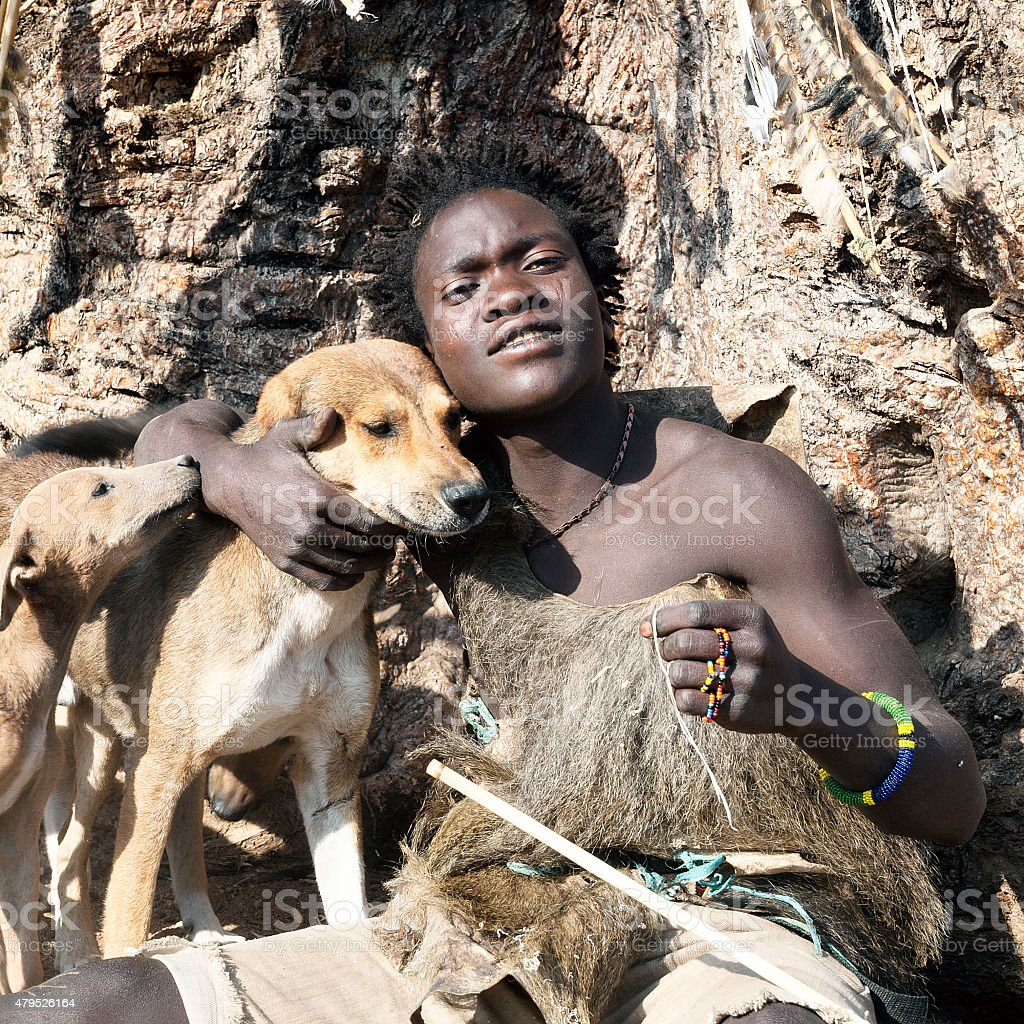 Hadzabe (or Hadza) young bushman with dogs stock photo