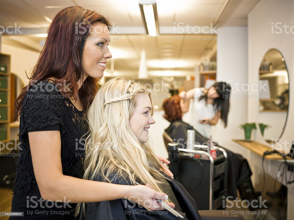 Hair dresser with young girl in the salon chair stock photo