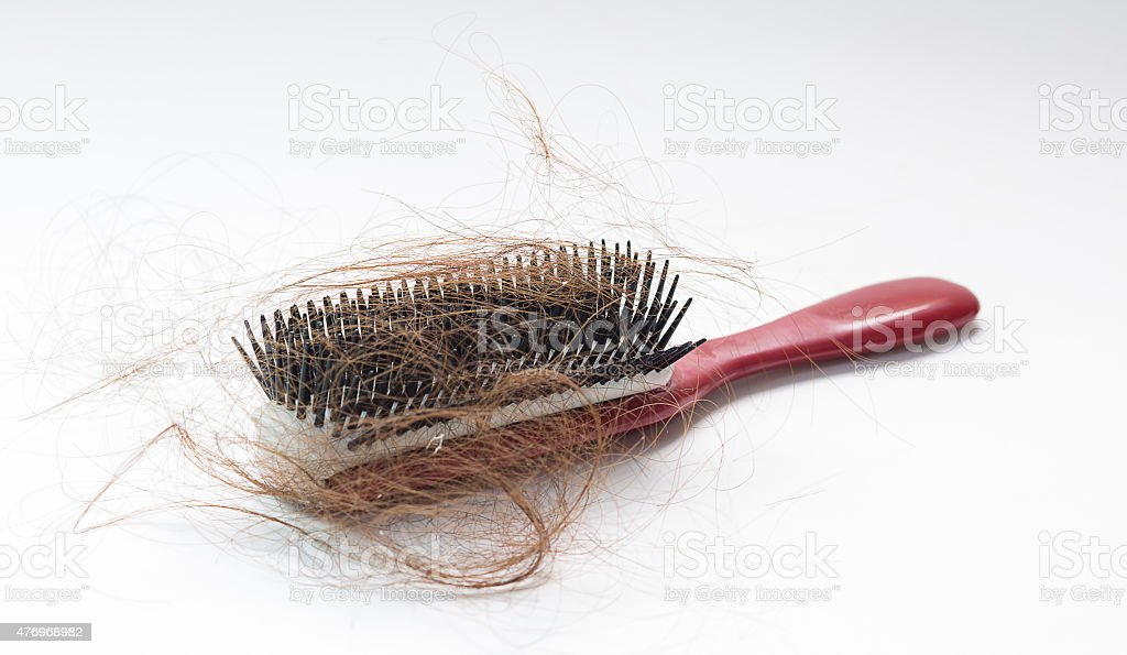 Hair fall on a red comb isolated on white background stock photo
