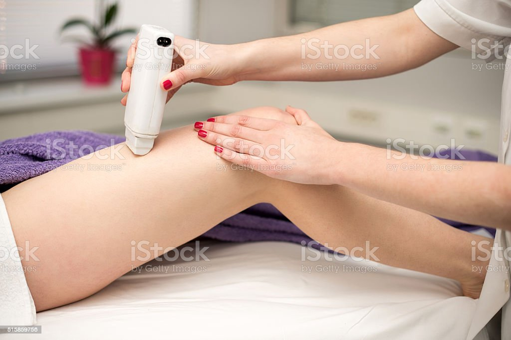 Hair removal cosmetology procedure from a therapist at cosmetic stock photo