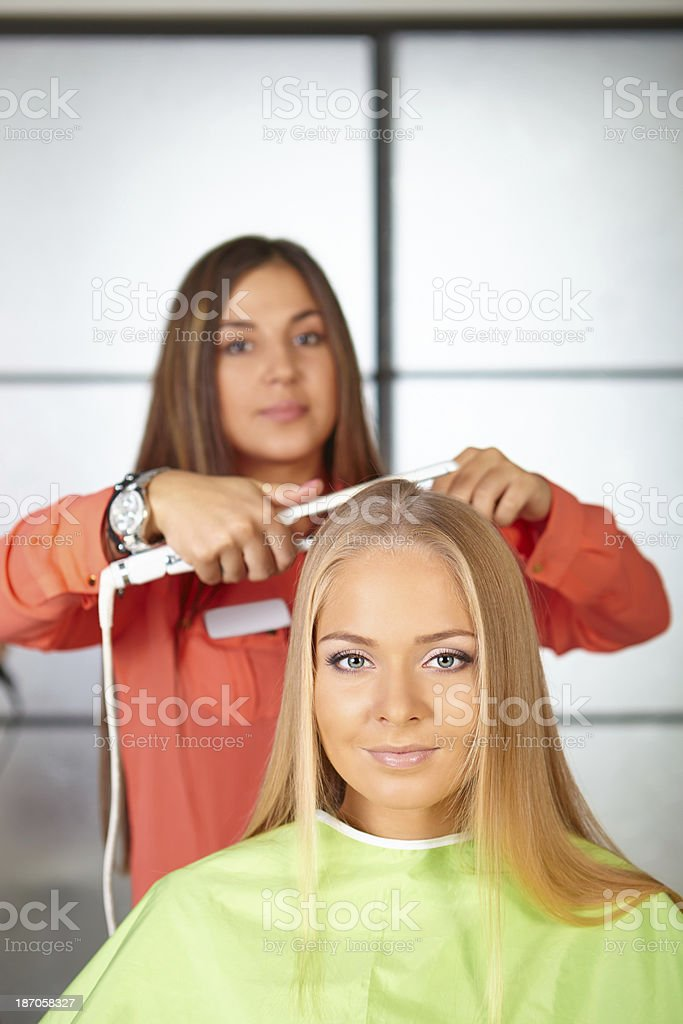 Hair salon. Women`s haircut. Use of straightener. royalty-free stock photo