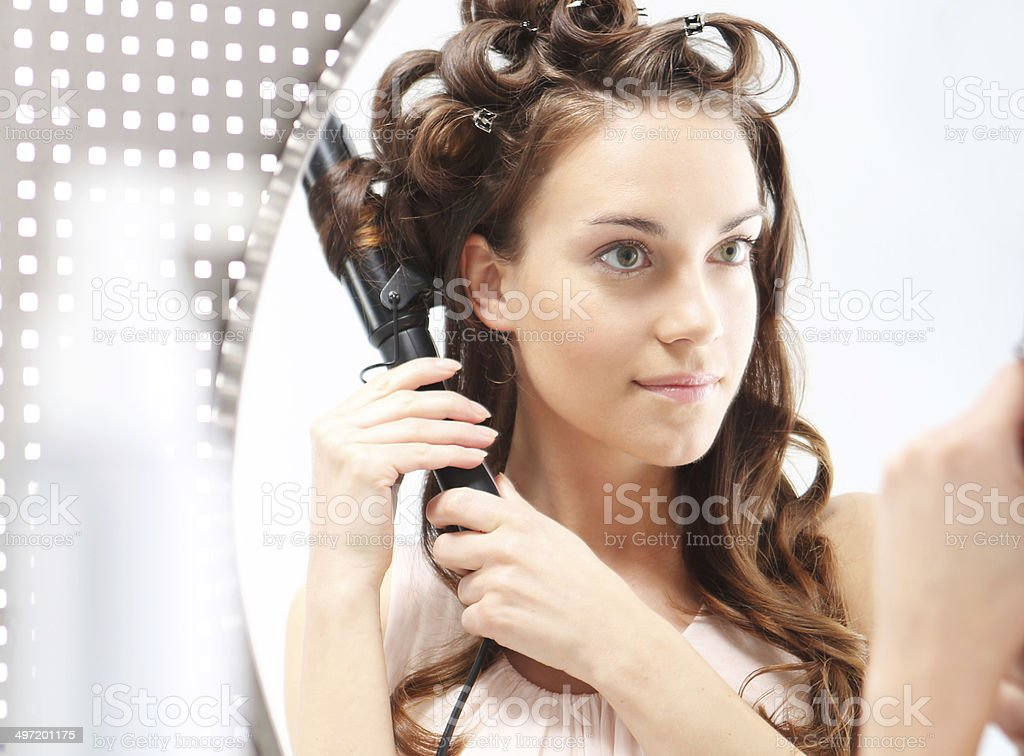 Hair Styling - brunette brushing her hair before a mirror stock photo