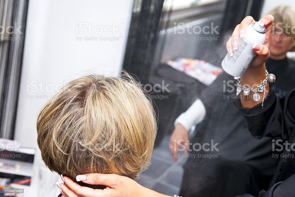 Hair Stylist Applying Hairspray stock photo