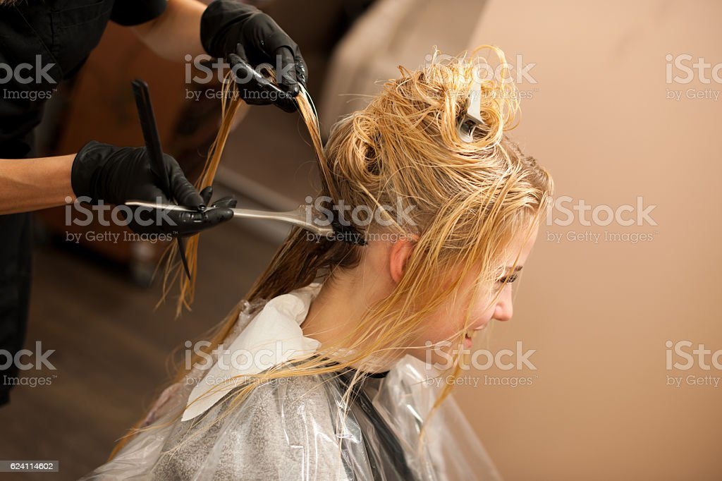 hair stylist at work - hairdresser  applying color on hair stock photo
