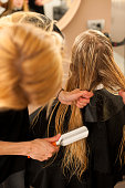 Hair stylist at work - hairdresser combing hair to customer