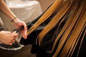 Hair stylist at work - hairdresser cutting hair to customer