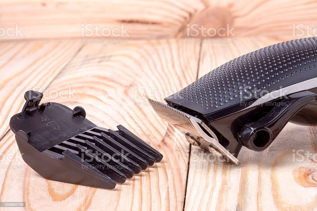 hair trimmer  with attachment on a light wooden background closeup stock photo