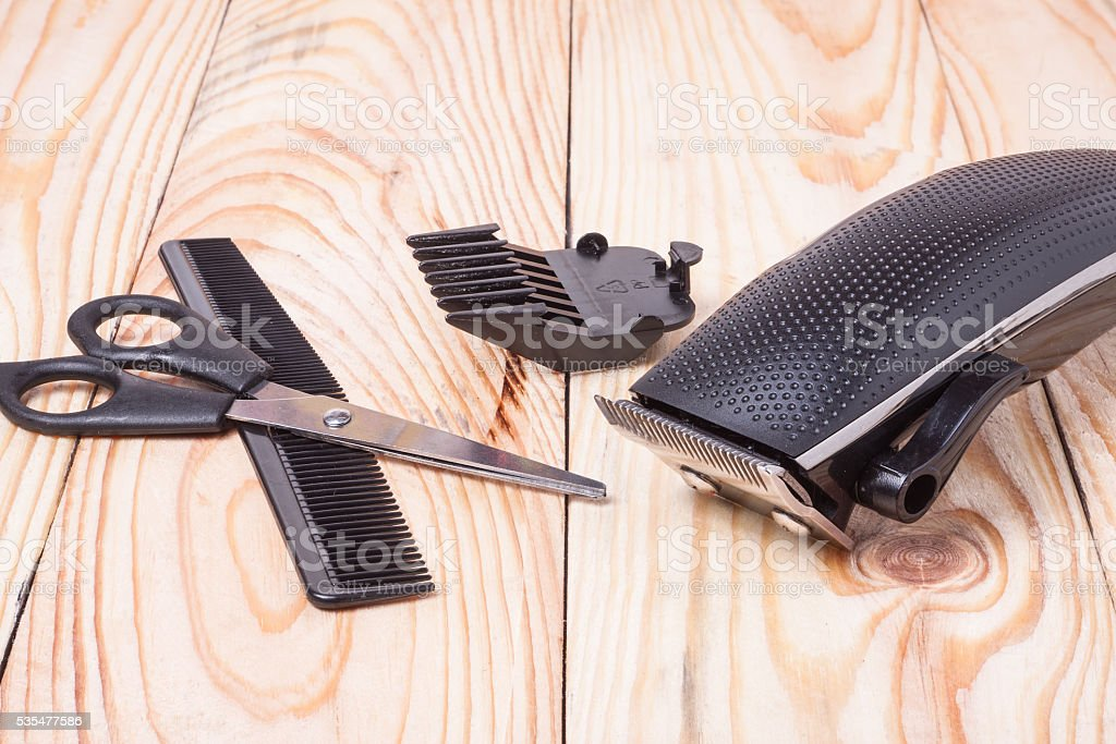 hair trimmer with comb and scissors on the wooden background stock photo