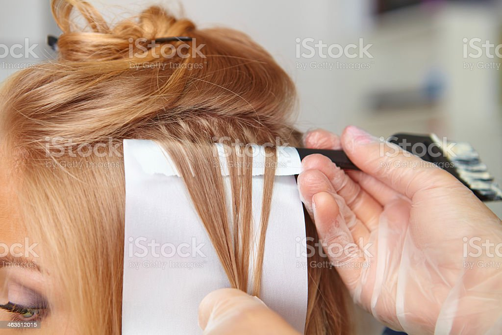 Hairdresser adding color to female's hair stock photo