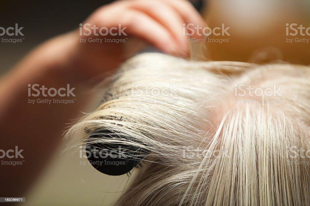 Hairdresser brushing blonde hair stock photo