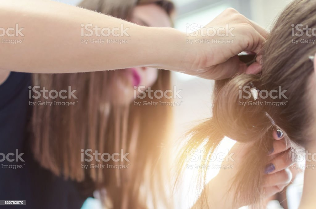 Hairdresser coiffeur makes hairstyle. stock photo
