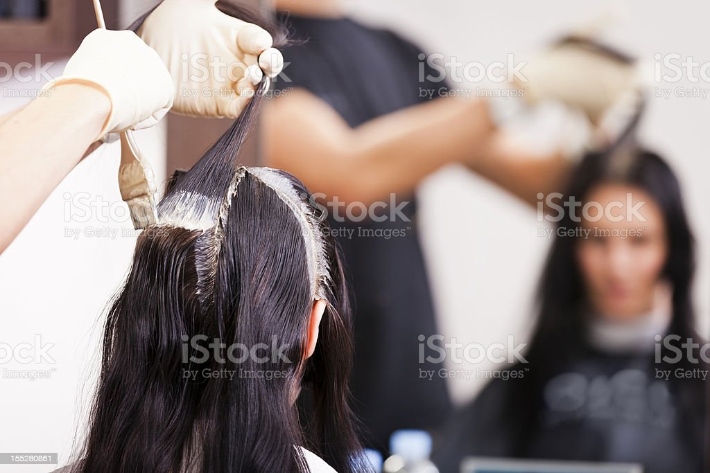 Hairdresser coloring hair roots stock photo