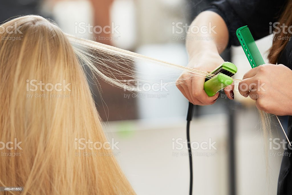 Hairdresser curling hair with straightener stock photo