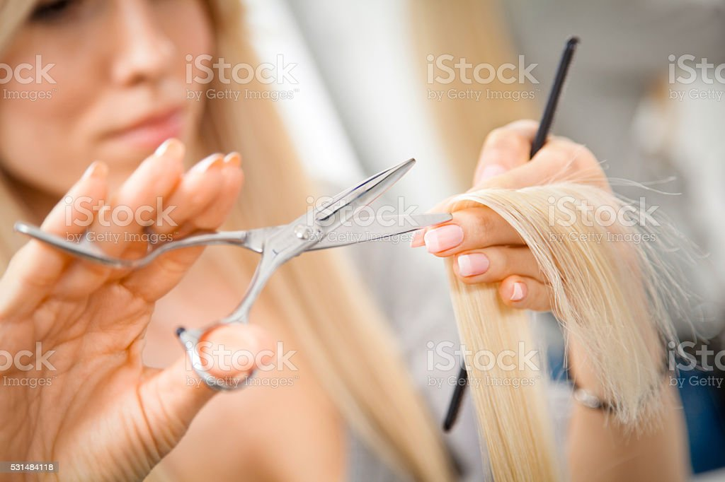 Hairdresser cutting client's hair in beauty salon. stock photo