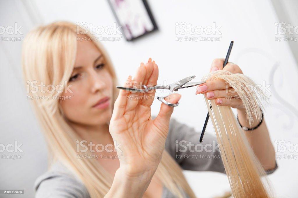 Hairdresser cutting customer's hair in salon. stock photo