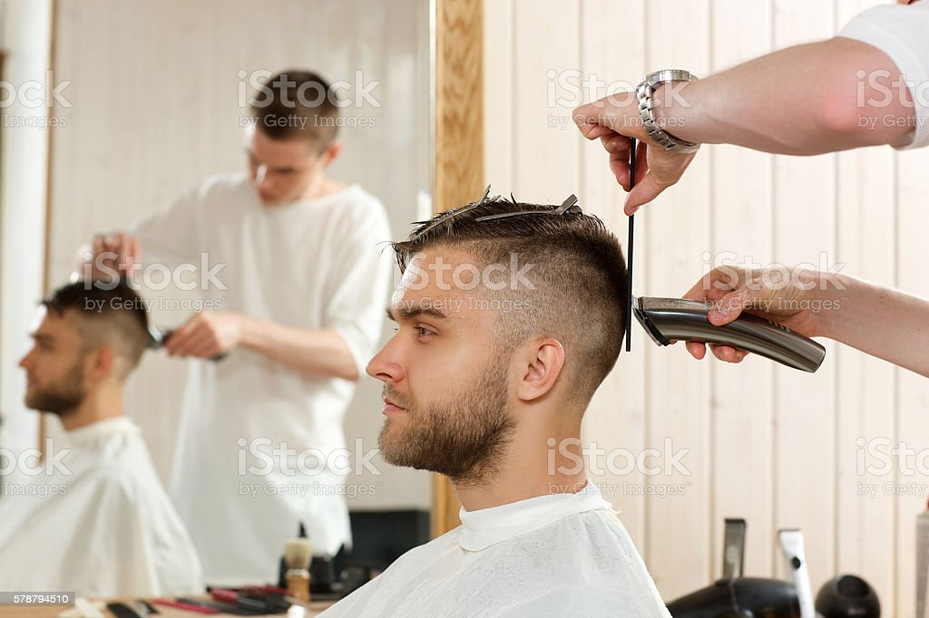 hairdresser cutting hair with hairclipper to his client stock photo