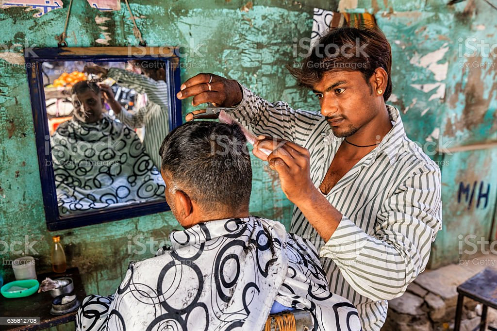 Hairdresser cutting man's hair on the streets of Jaipur, Rajasthan stock photo