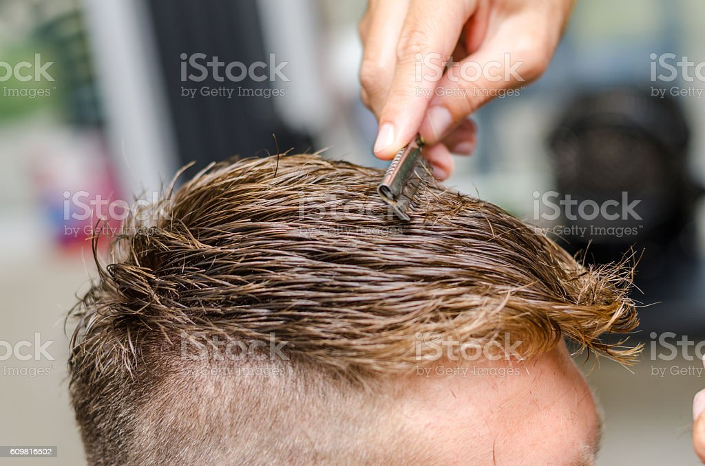 Hairdresser cutting man's hair with toothed razor stock photo