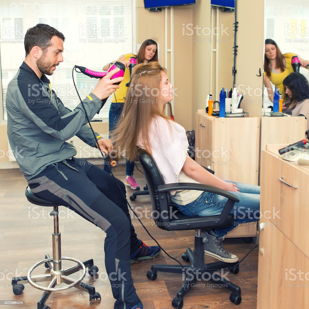 Hairdresser drying his client's hair stock photo