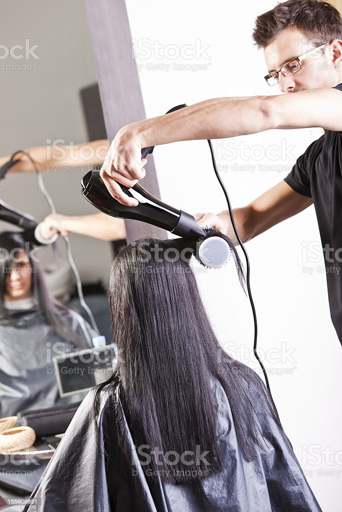 Hairdresser drying woman's hair after washing royalty-free stock photo