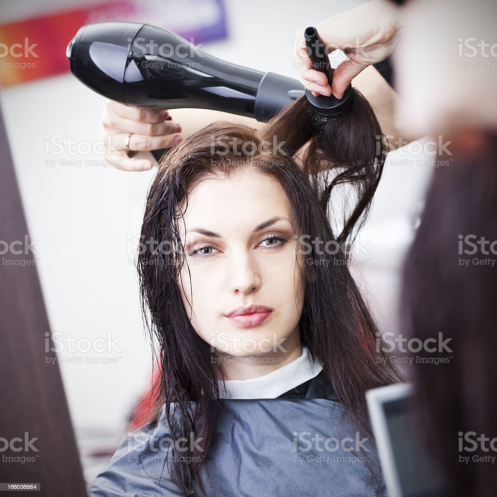 Hairdresser drying woman's hair stock photo